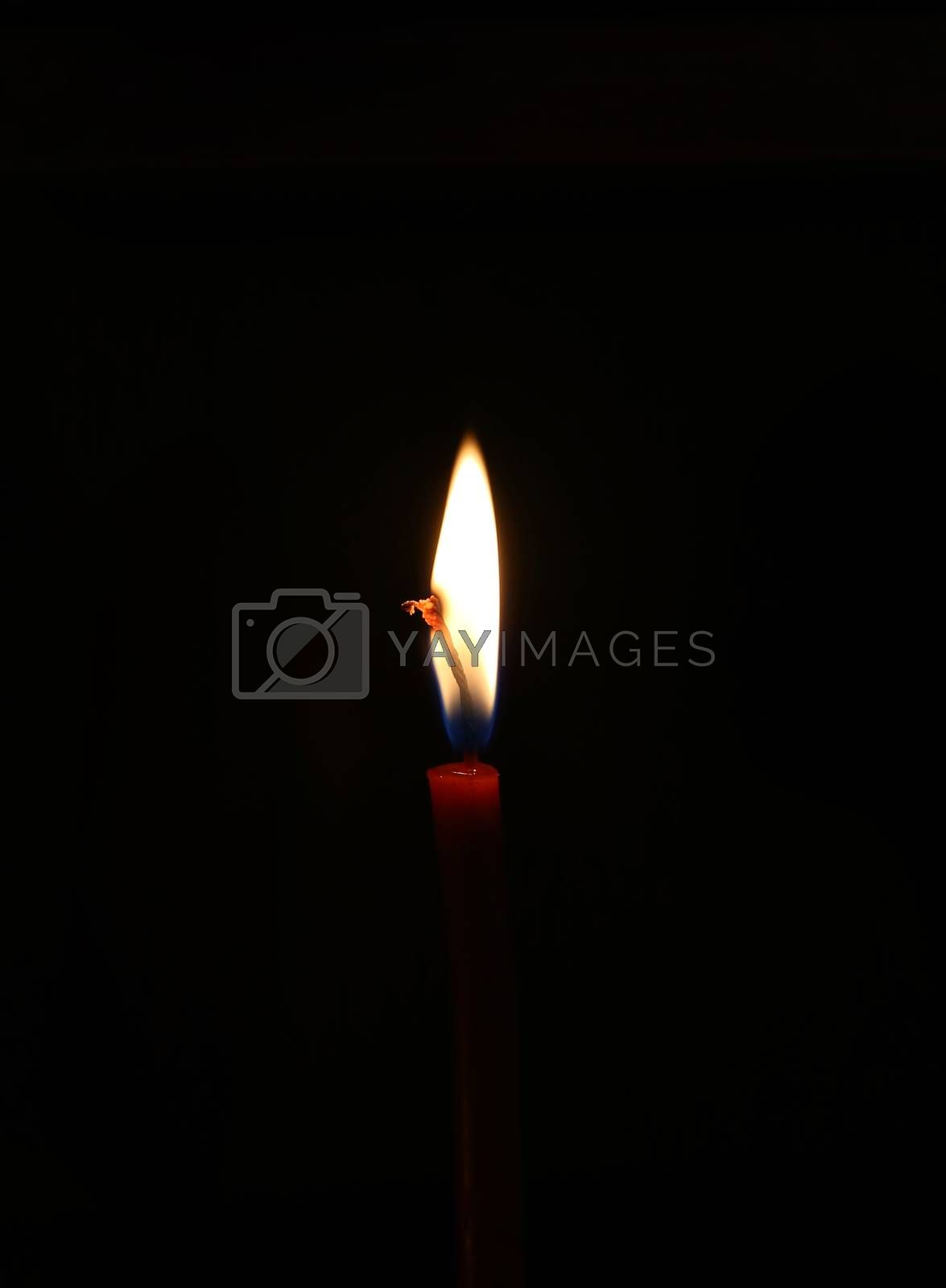 Closeup of bright burning candle in the dark