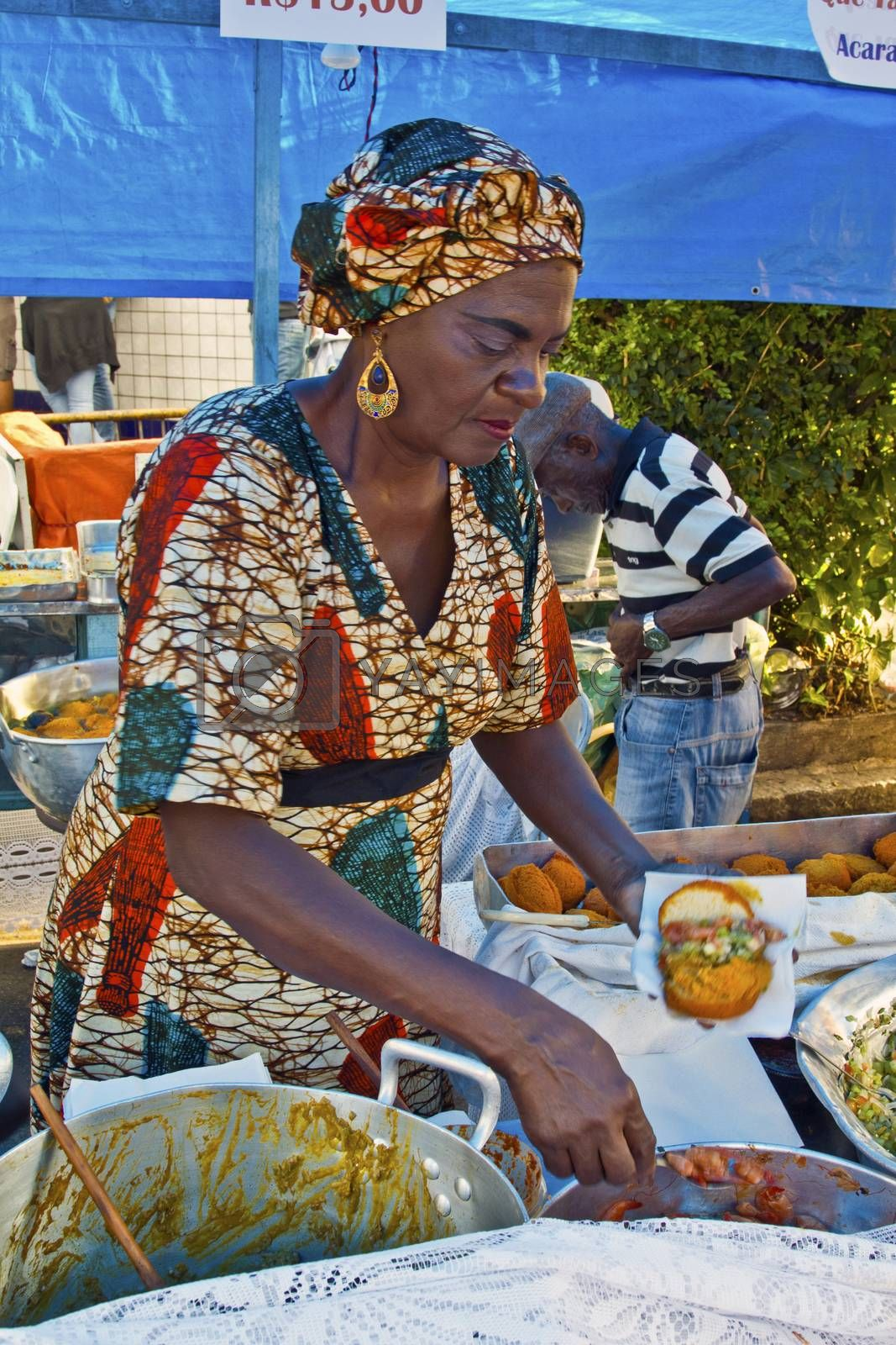 SAO PAULO, BRAZIL - MAY 17, 2015: An unidentified woman preparing typical brazilian food in a stand at a street fair market in Sao Paulo.