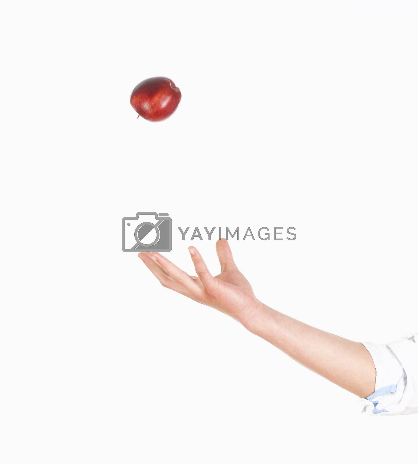 Royalty free image of Hand Tossing Red Apple in the Air  by courtyardpix