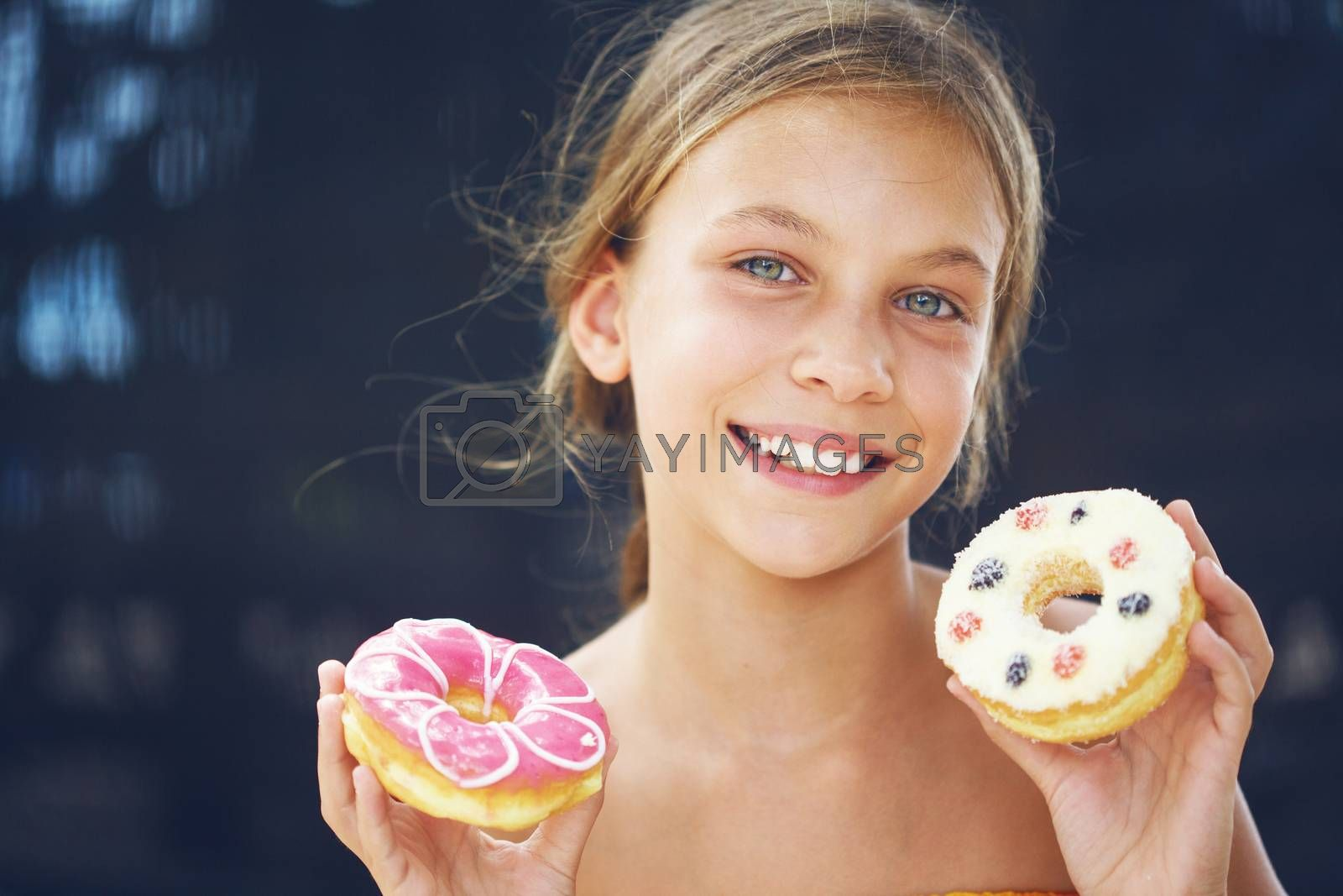 Cute kid girl eating sweet donuts