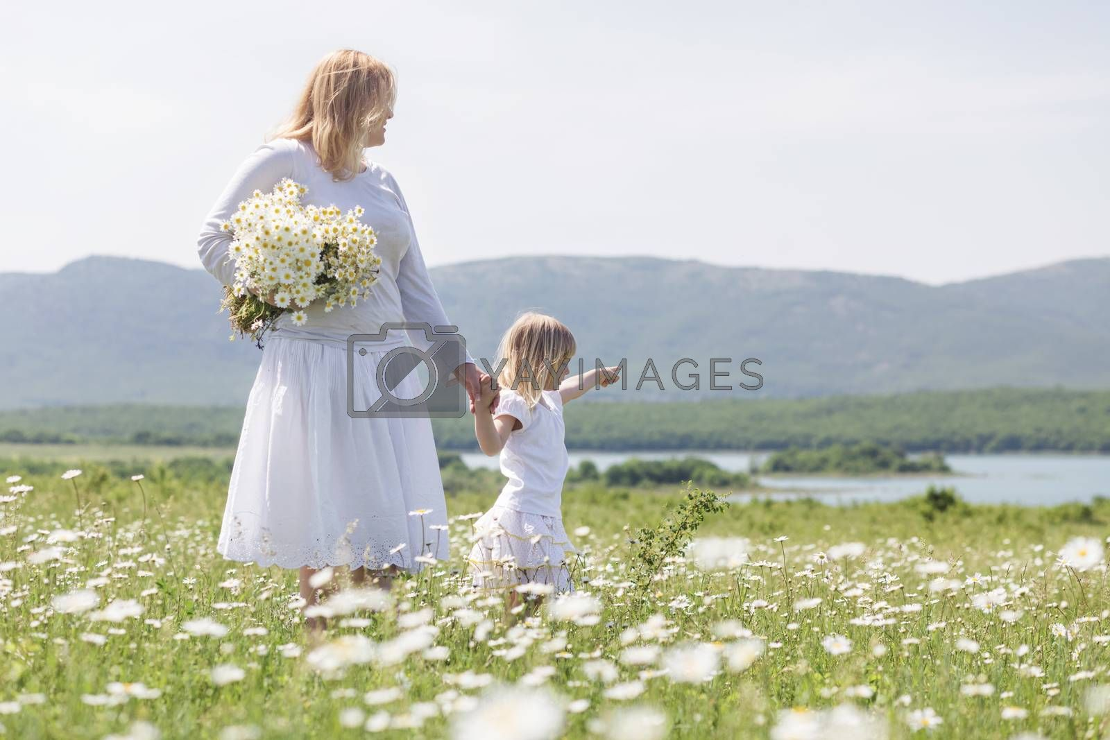 Happy mother playing with her daughter in flower field