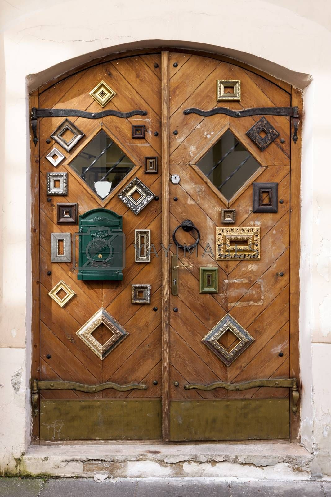 Vertical oriented picture of wooden shop doors decorated with a set of antique picture frames. Original shot made in Vilnius, capital of Lithuania