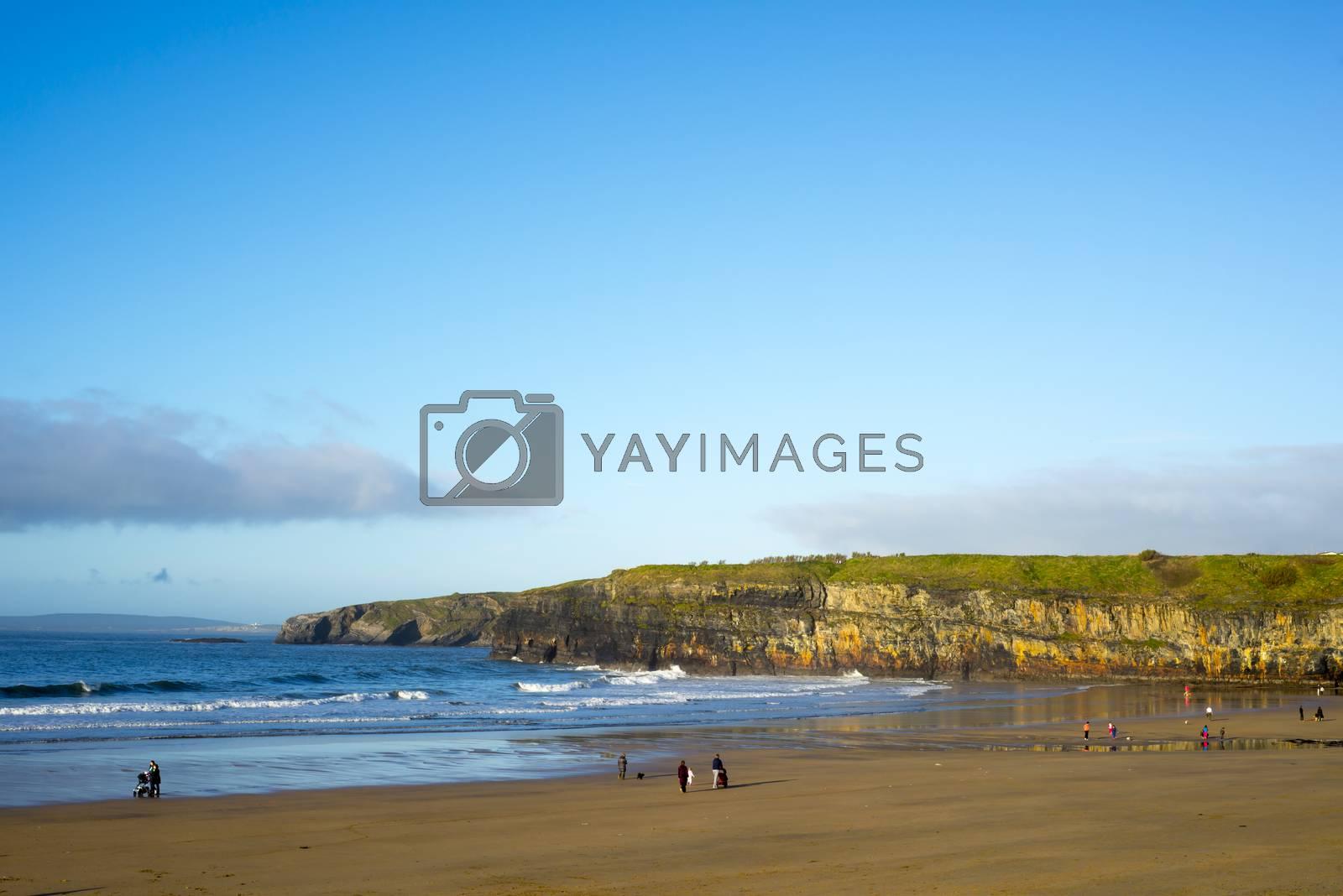 people enjoying a walk on Ballybunion beach one bright winters day