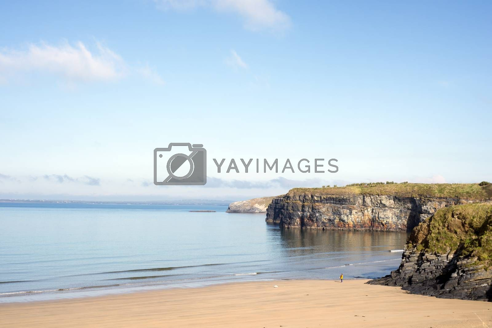 woman walking a dog as soft waves break on the beach cliffs at ballybunion