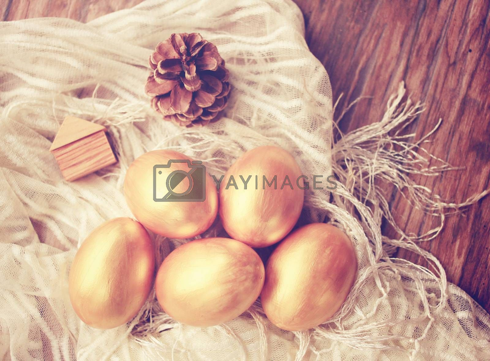Gold easter eggs and decorated on wood background with retro filter effect