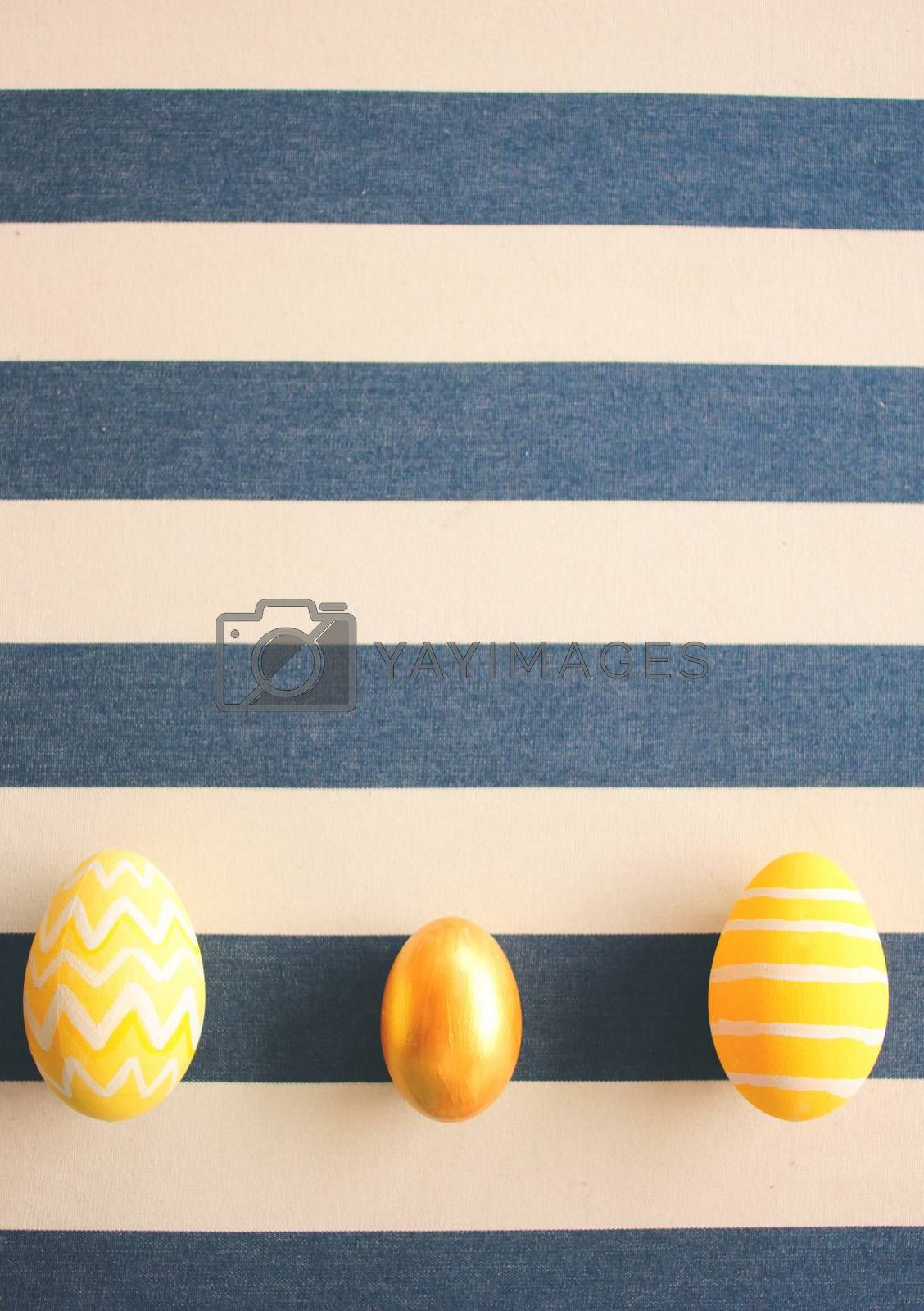 Yellow easter eggs on striped background with retro filter effect