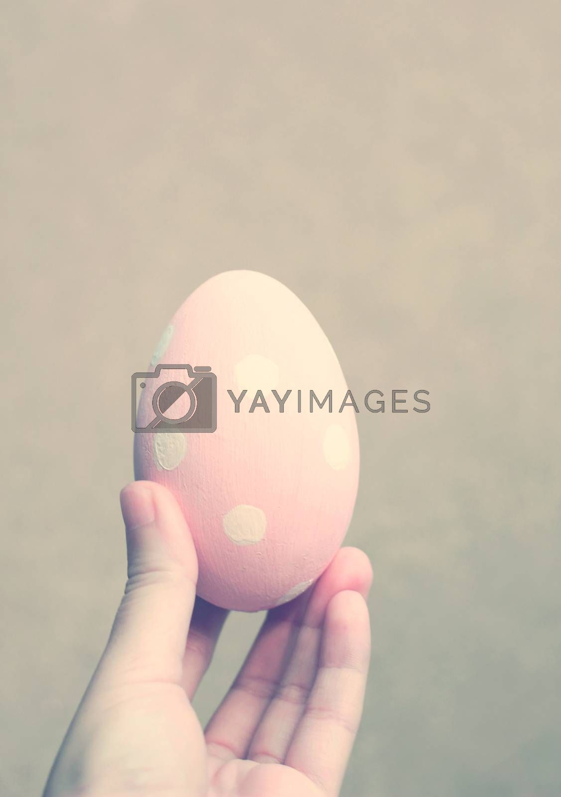 Hand holding painted easter egg with retro filter effect