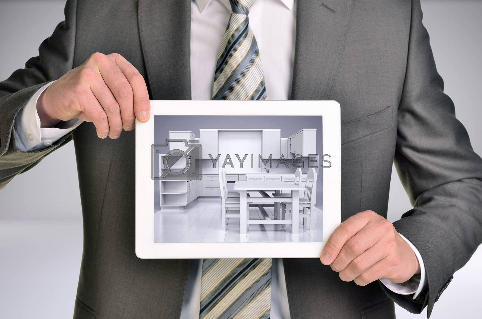 Three-dimensional model of kitchen in tablet screen. Man holding tablet in hand. Gray background