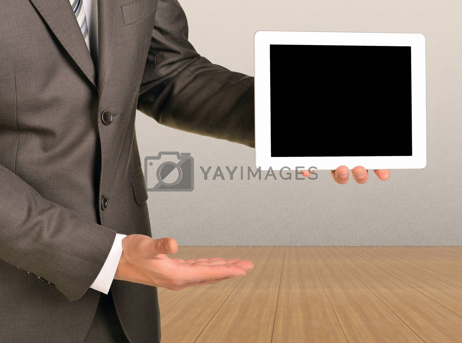 Your concept on the tablet. Man holding tablet. Wooden floor and gray wall in background