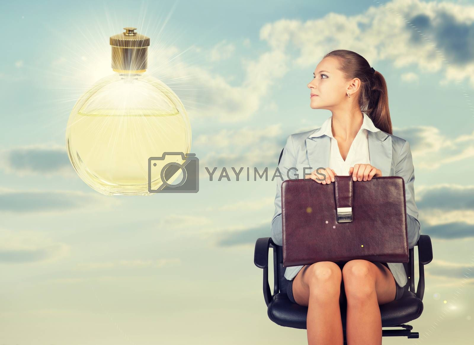 Business woman in skirt, blouse and jacket, sitting on chair and holding briefcase imagines perfume. Against background of sky and clouds