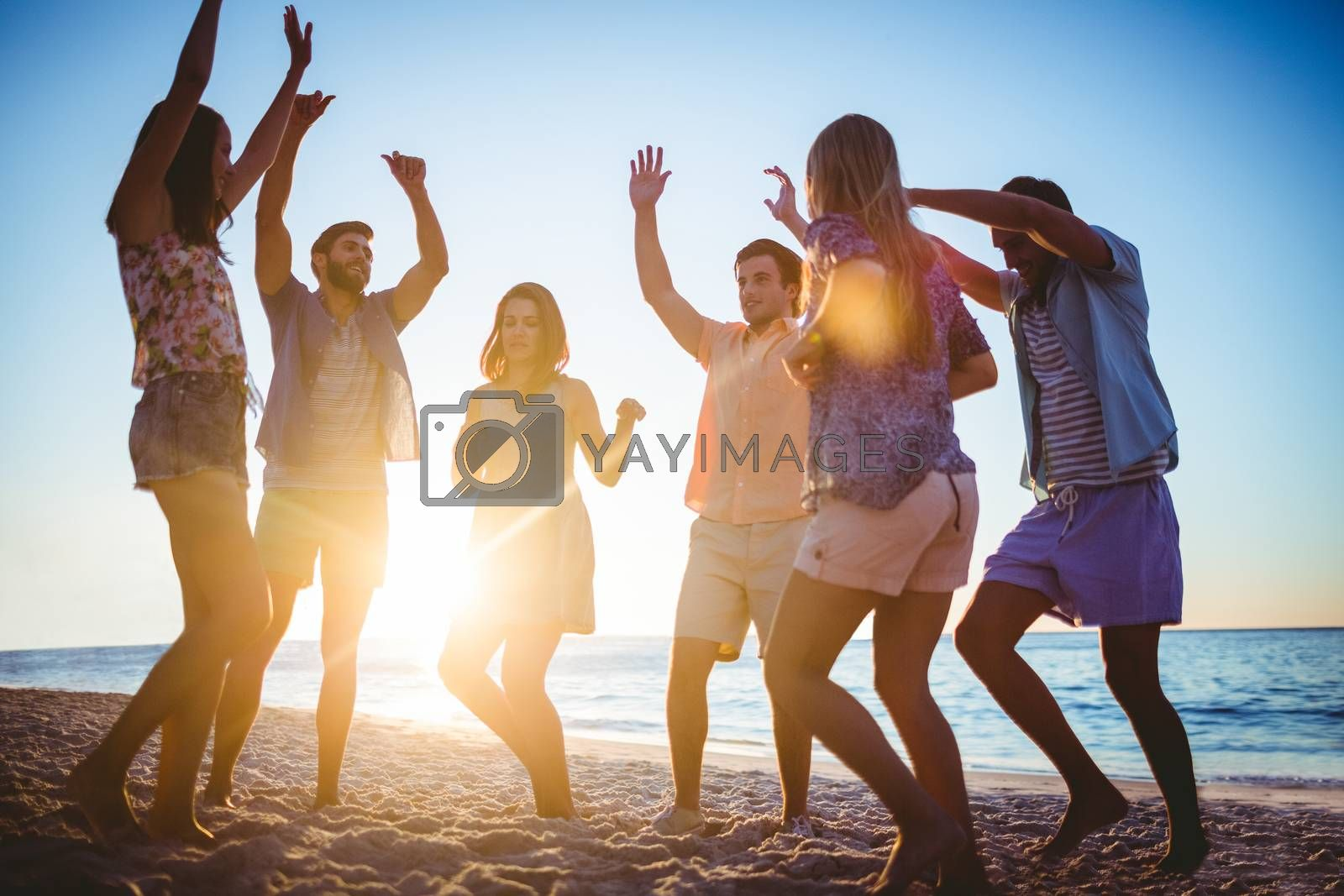 Happy friends dancing on the sand at the beach