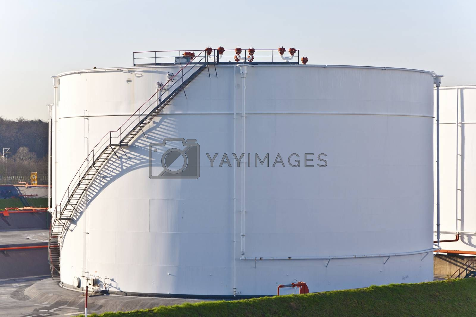 white tanks in tank farm with blue sky by meinzahn