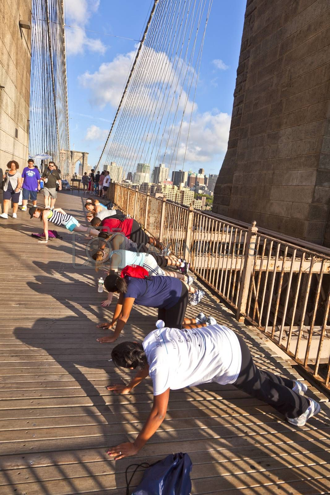 NEW YORK, USA - JULY 9, 2010: people exercise push-up at Brooklyn bridge in New York, USA. Brooklyn Bridge was constructed under Roeblings 1840 patent for the in-situ spinning of wire rope.