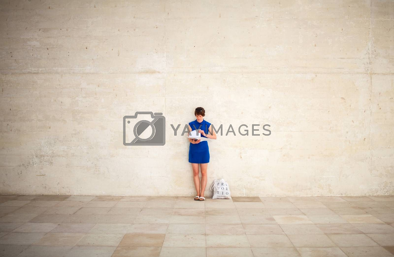 VENICE, ITALY - MAY 06: Girl leaning against the wall reading during the 56th Venice Biennale on May 06, 2015