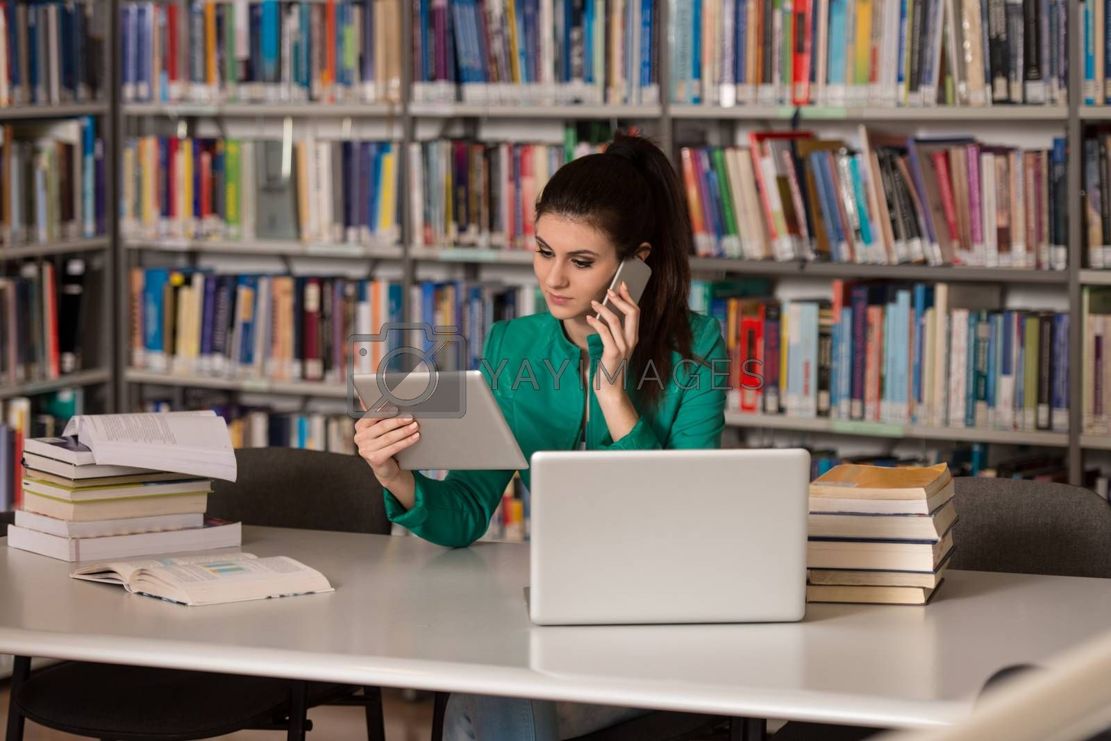 Female Student Talking On The Phone In Library - Shallow Depth Of Field