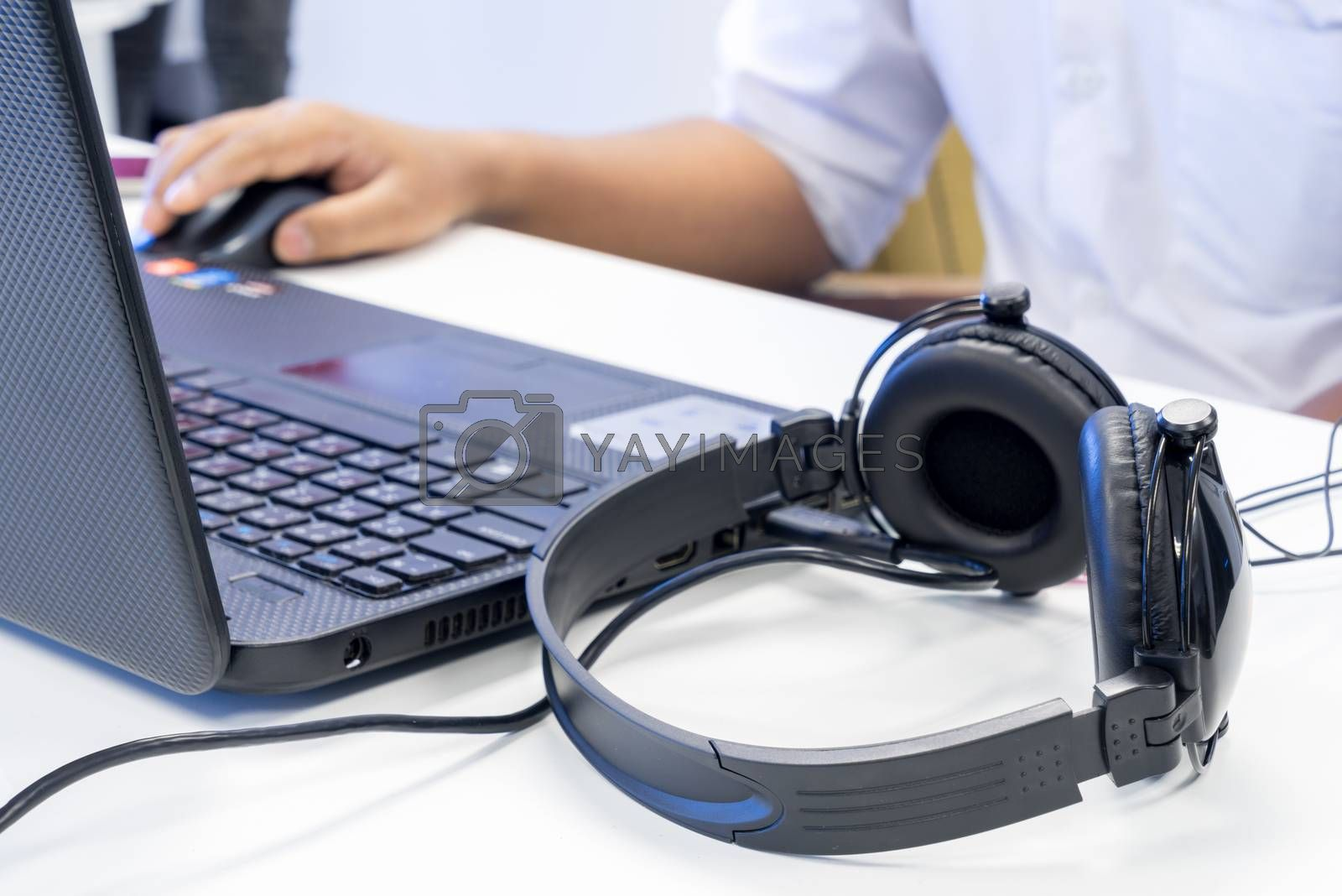 Royalty free image of Man hand using keyboard and mouse to control laptop with headpho by iamway