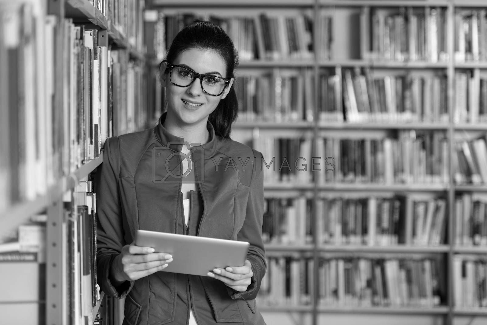In The Library - Pretty Female Student With Tablet And Books Working In A High School - University Library - Shallow Depth Of Field