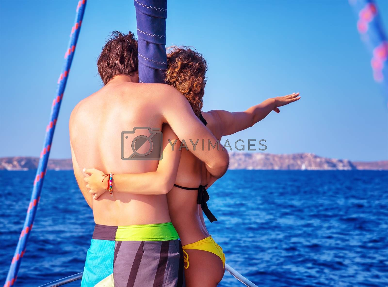 Back side of happy couple in love traveling on luxury sail boat along sea, romantic honeymoon vacation, summer travel and tourism