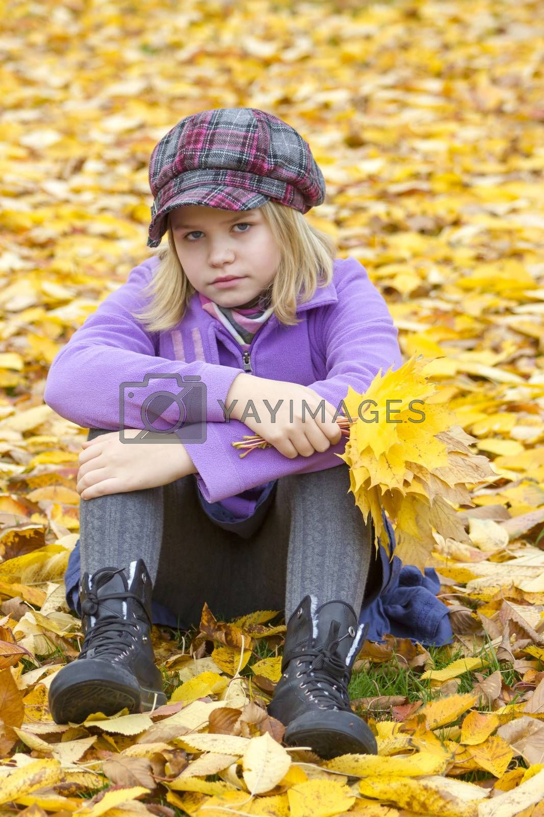 little girl sitting on leaves in the park by miradrozdowski