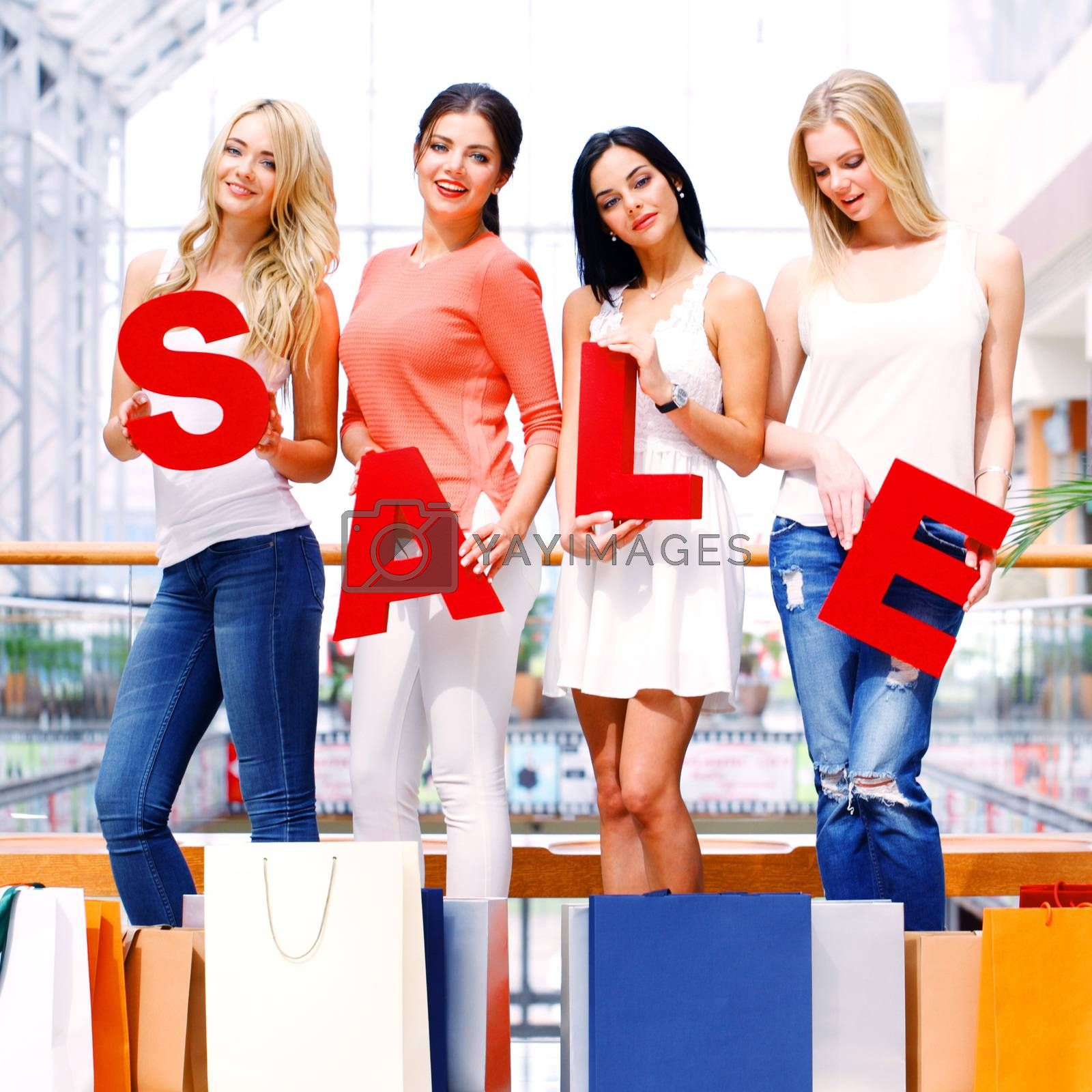 beautiful young women holding SALE letters