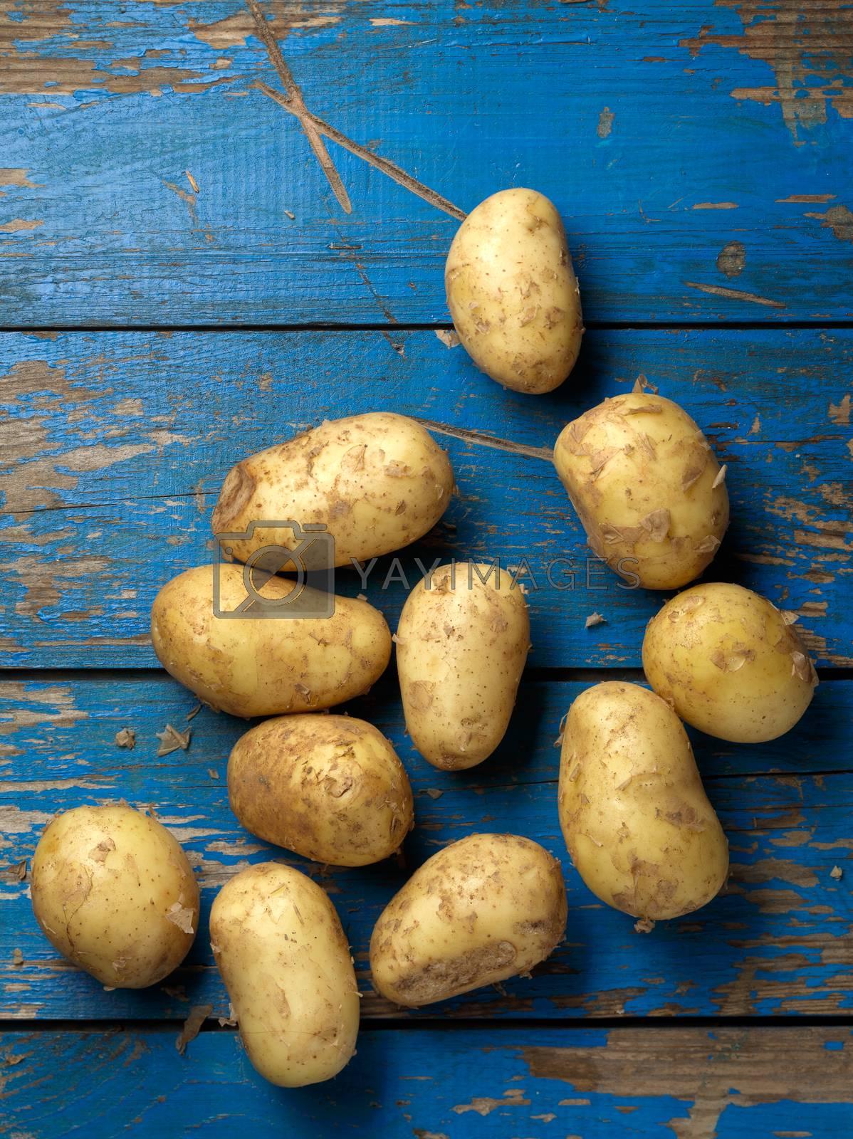 fresh and ripe raw potatoes on woodem bleu plank