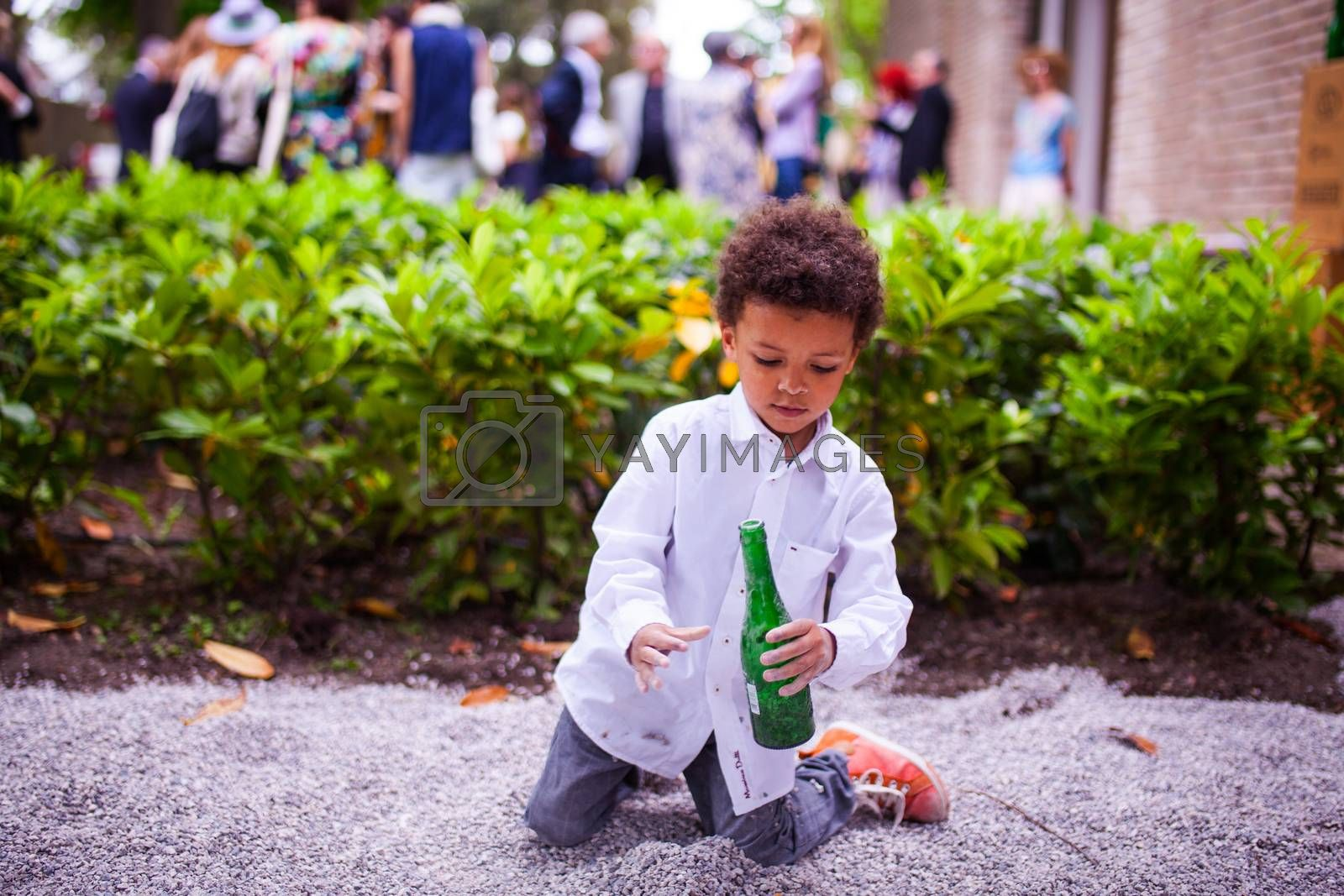 VENICE, ITALY - MAY 06: Child in the street playing with beer bottles on May 06, 2015