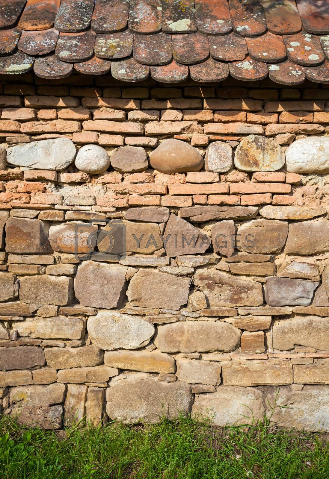 Rustic wall with layers of different comstruction materials - sandstones, bricks, river stones and roof tiles