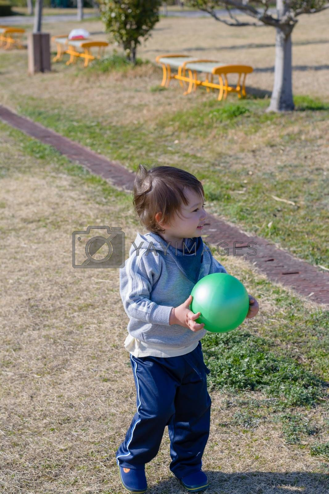 A 2 year old boy holding a ball and smiling at a playground.