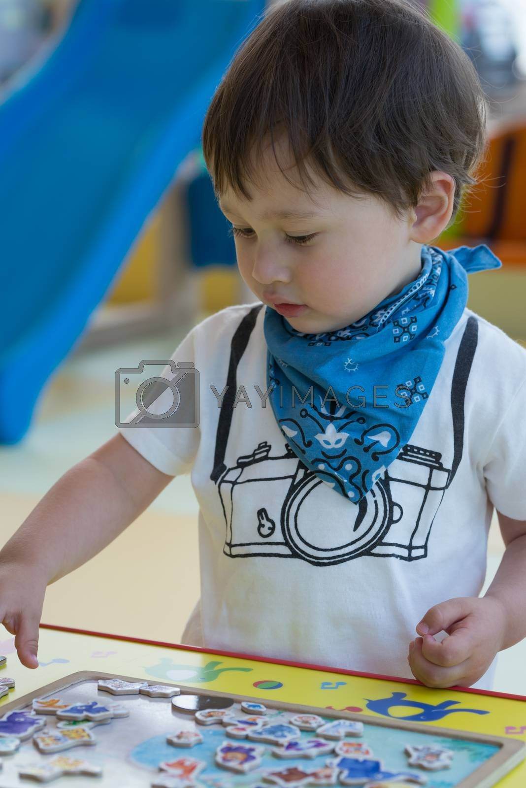 A cute young boy with a camera design t-shirt making a puzzle of many animals.