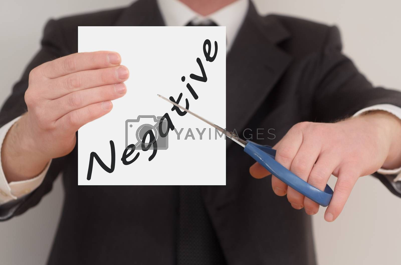 Negative, man in suit cutting text on paper with scissors