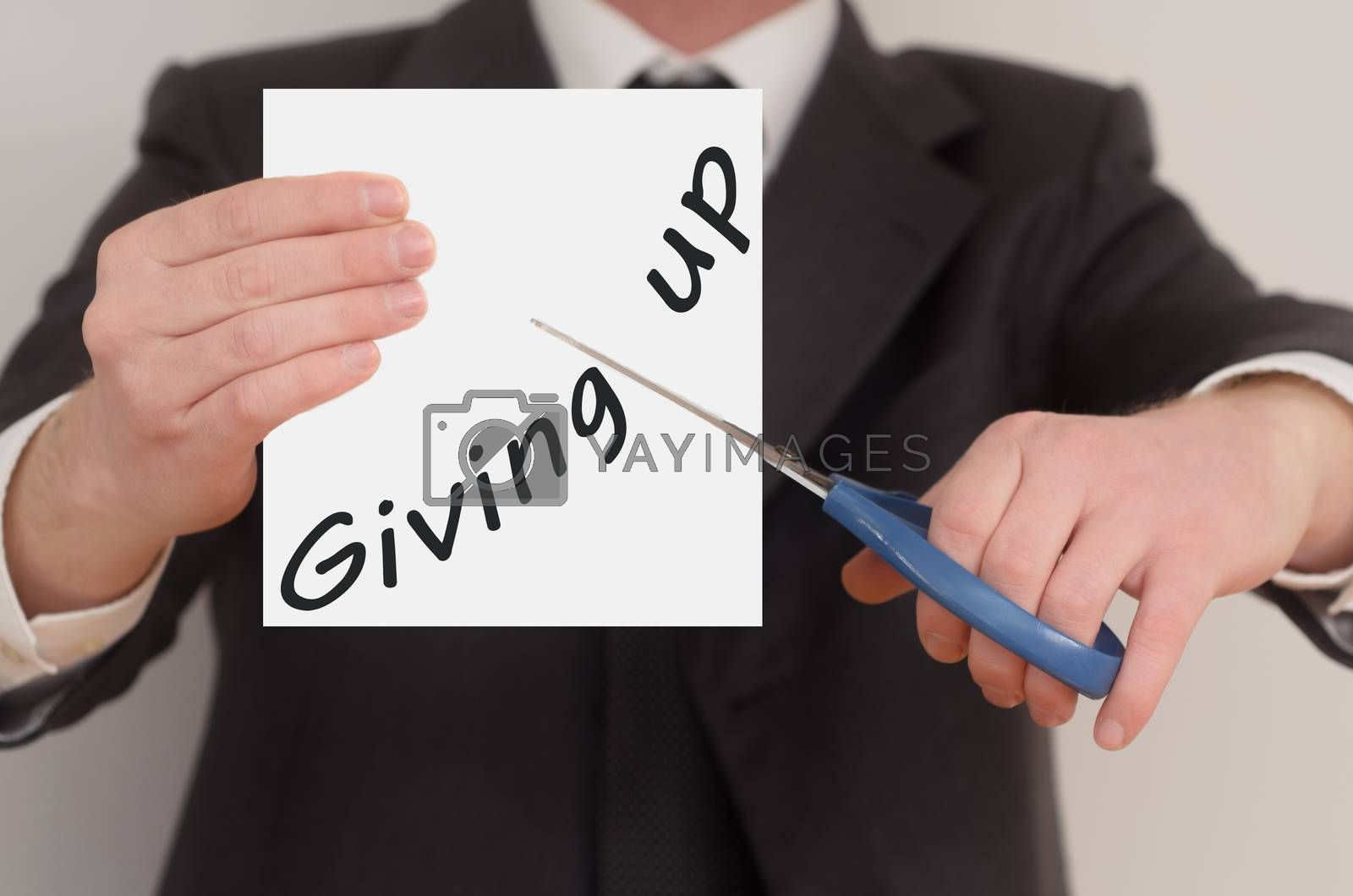 Giving up, man in suit cutting text on paper with scissors
