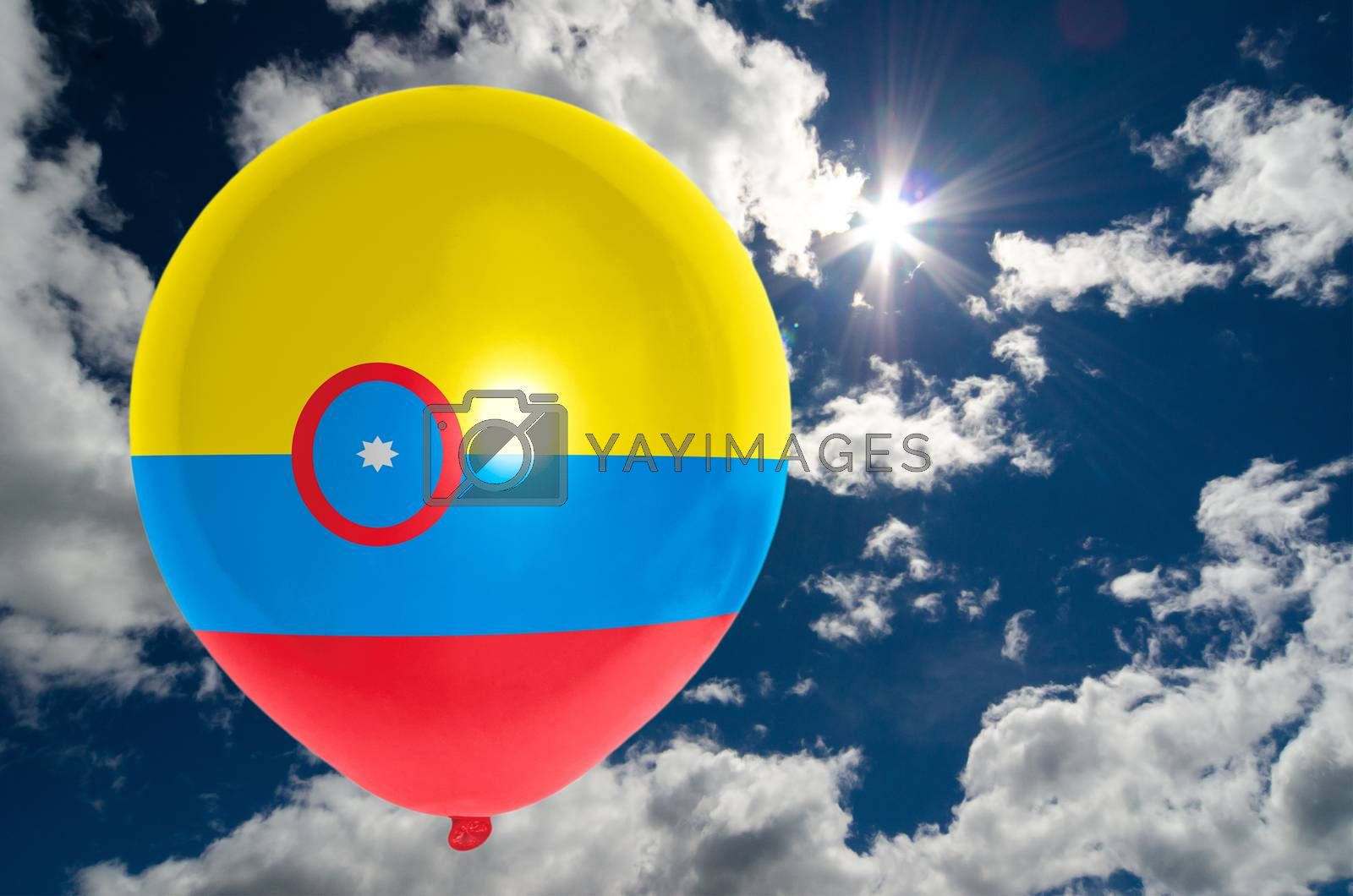 balloon in colors of colombia flag flying on blue sky