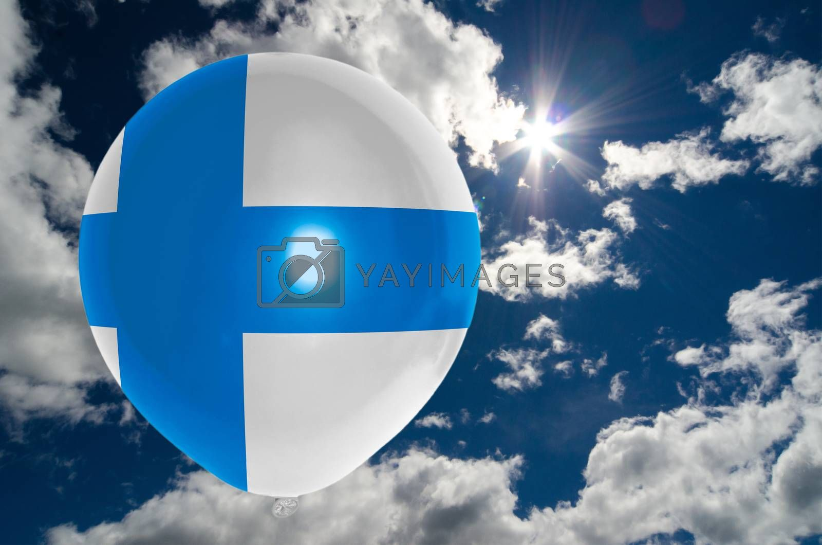 balloon in colors of finland flag flying on blue sky