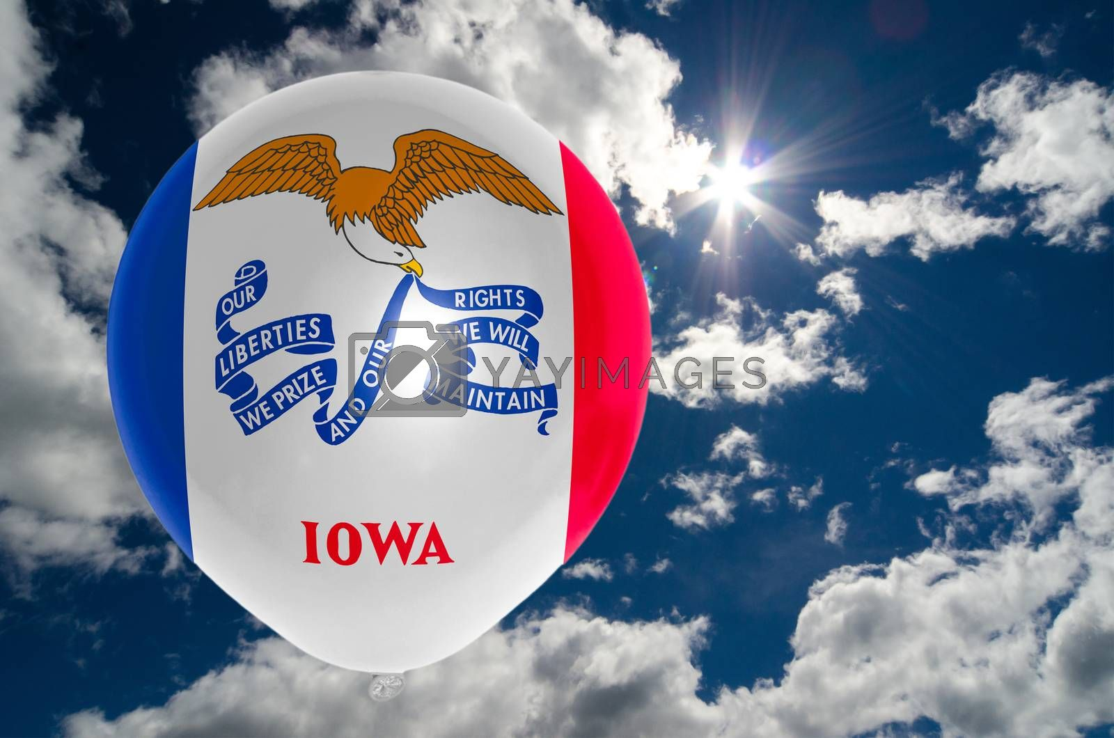 balloon in colors of iowa flag flying on blue sky