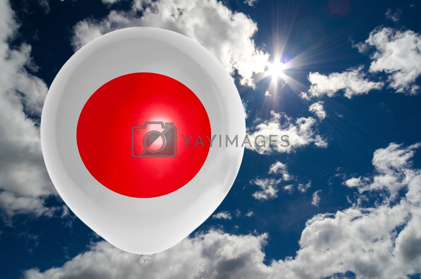 balloon in colors of japan flag flying on blue sky