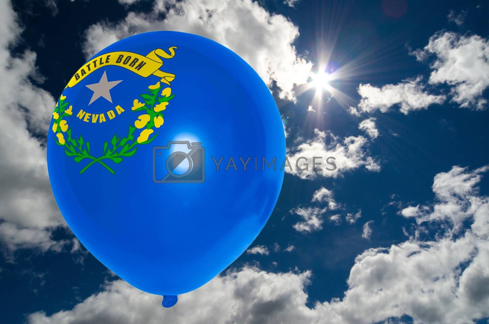 balloon in colors of nevada flag flying on blue sky