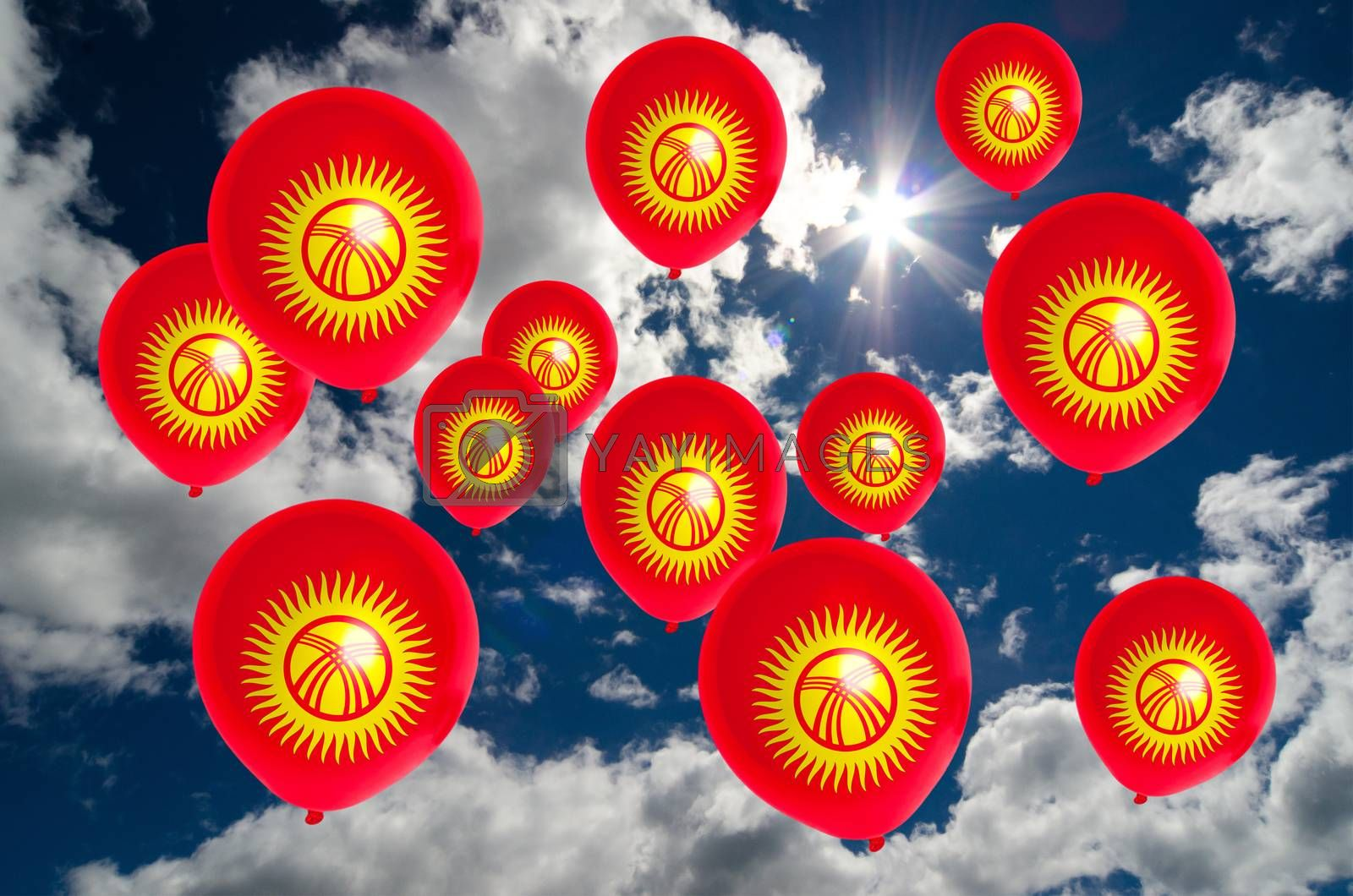 many ballons in colors of kirghizstan flag flying on sky