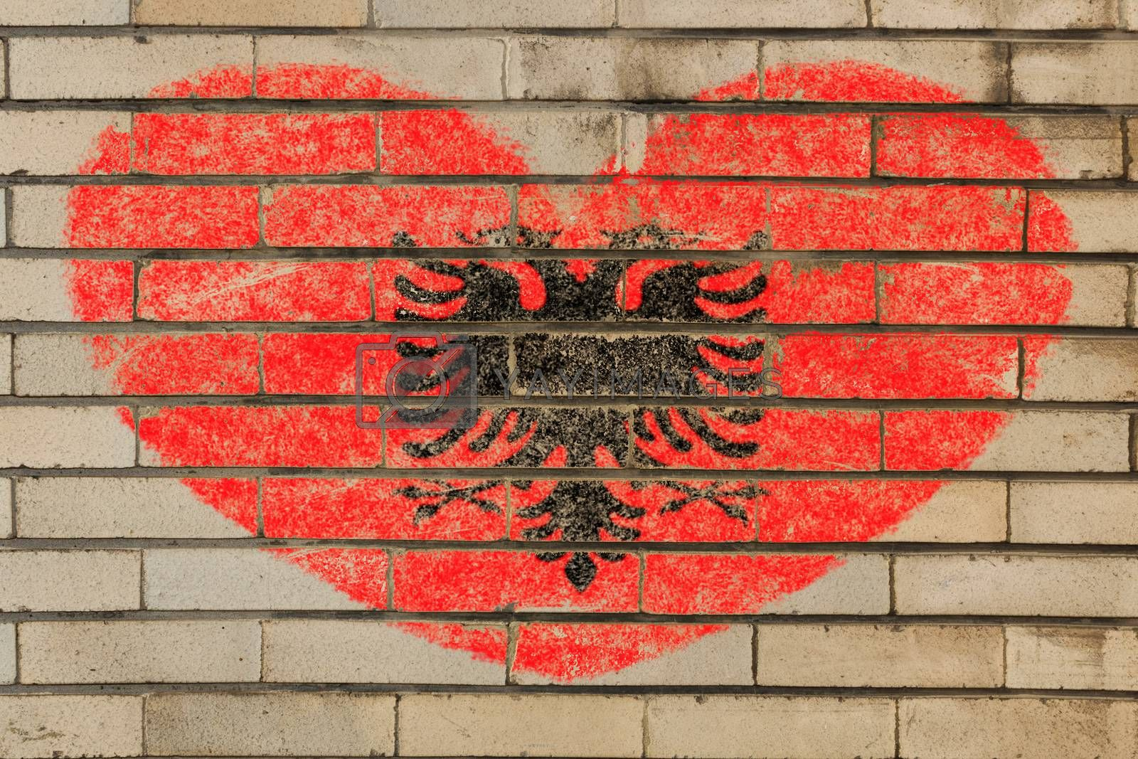 heart shaped flag in colors of albania on brick wall