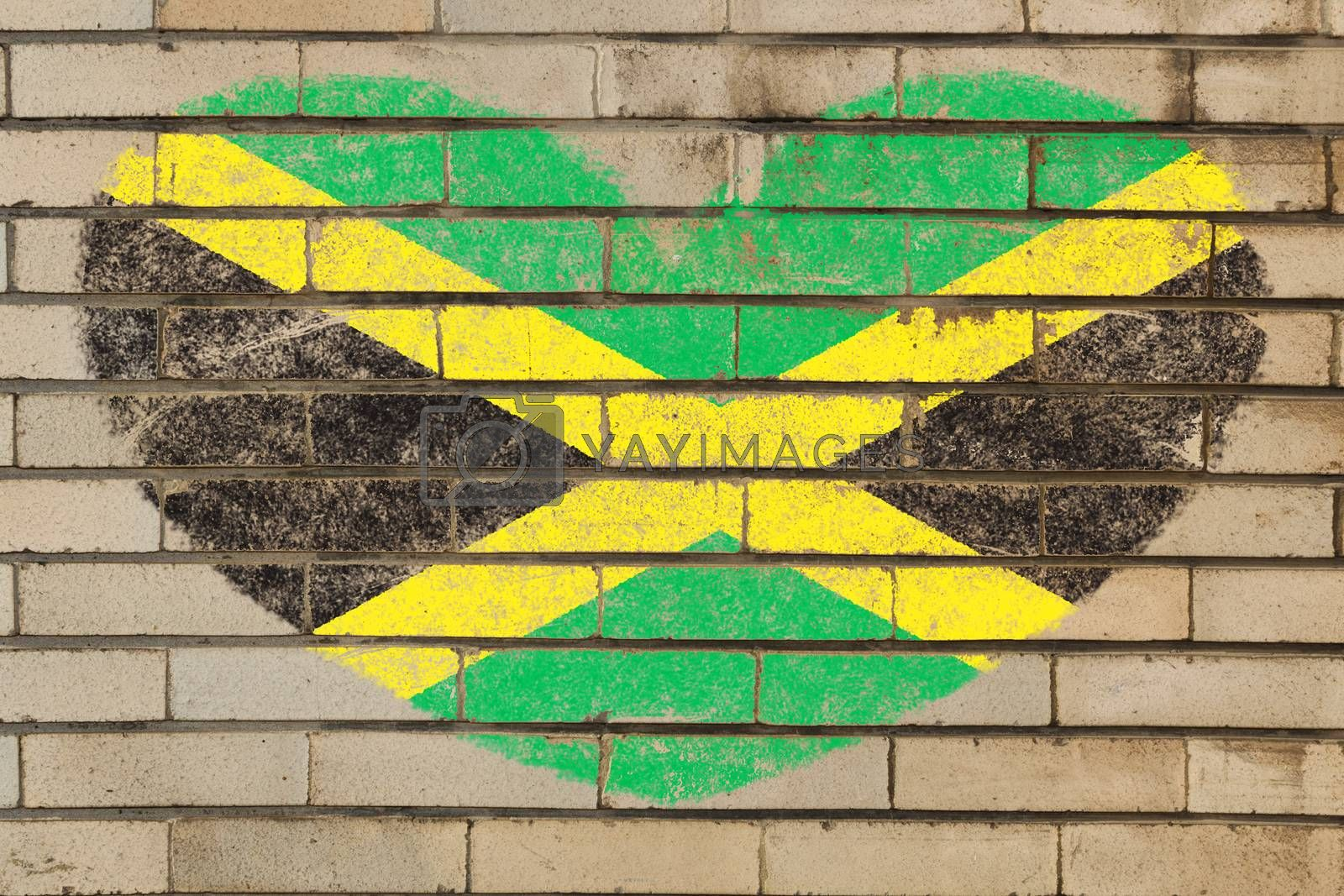 heart shaped flag in colors of jamaica on brick wall