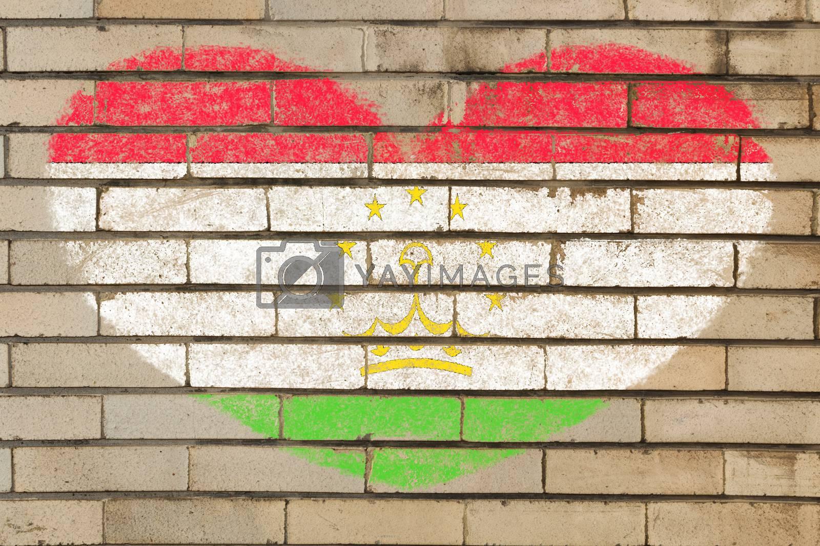 heart shaped flag in colors of tajikistan on brick wall