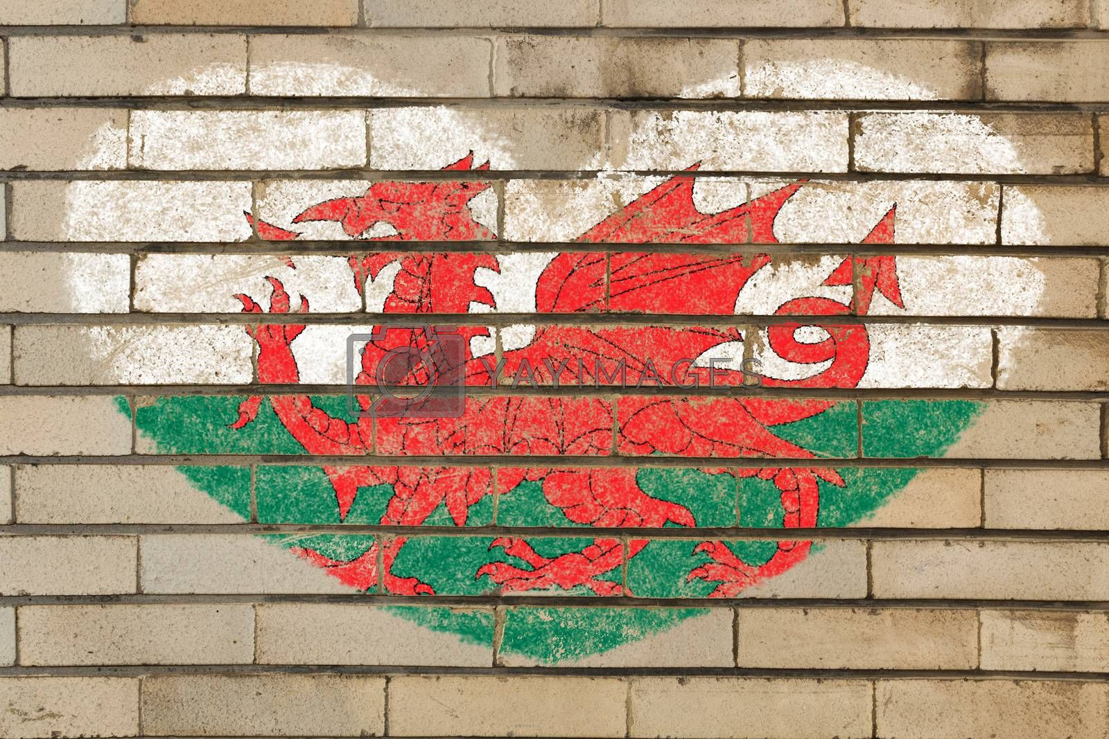 heart shaped flag in colors of wales on brick wall