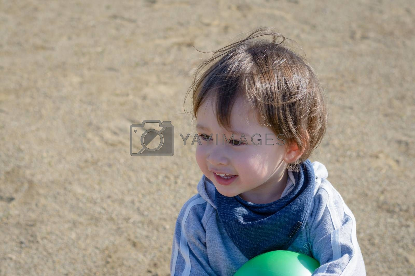 A 2 year old boy holding a green ball smiling in a playground.