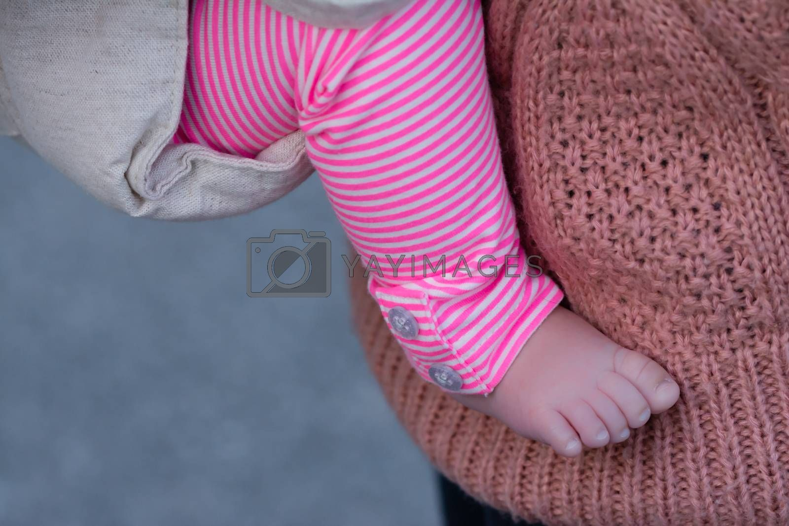 The foot and leg of a baby girl being carried by her mother, both wearing pink.