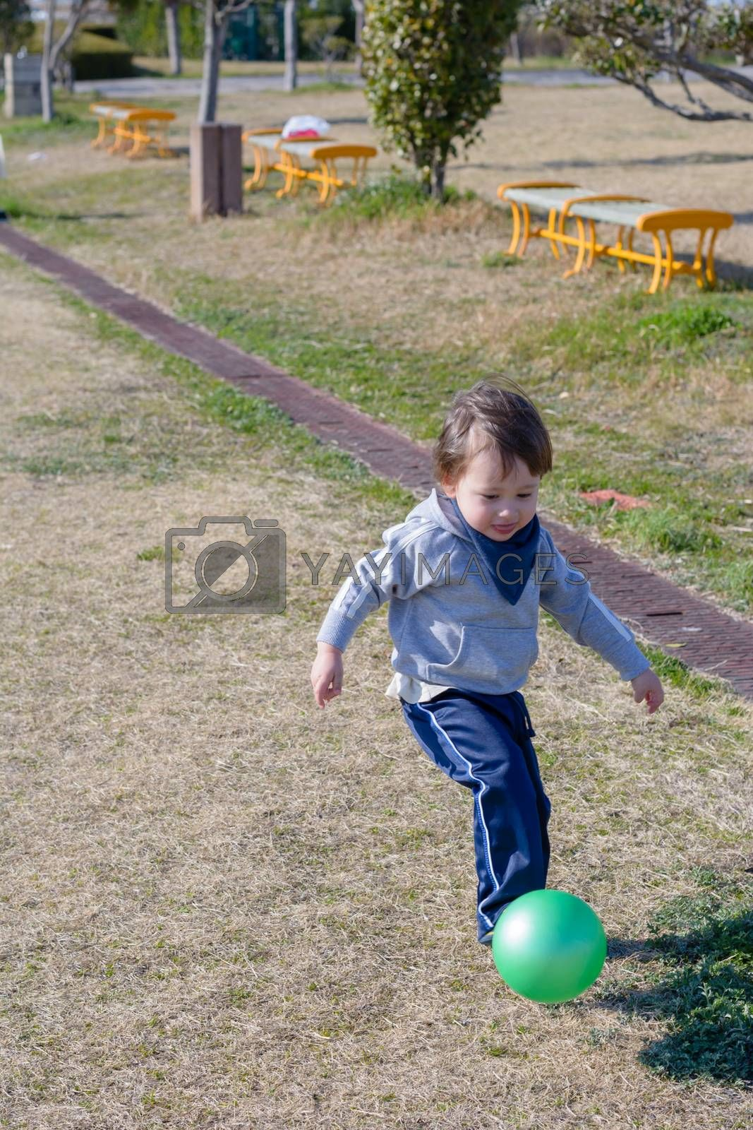 A 2 year old boy kicking a ball in a park.