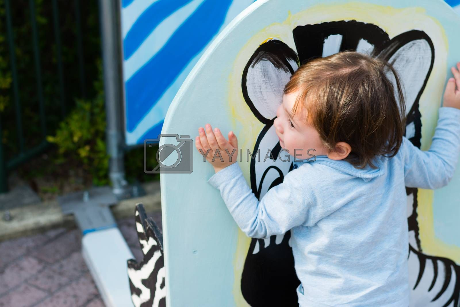 A 2 year old boy hugging a painting of a zebra at a zoo.