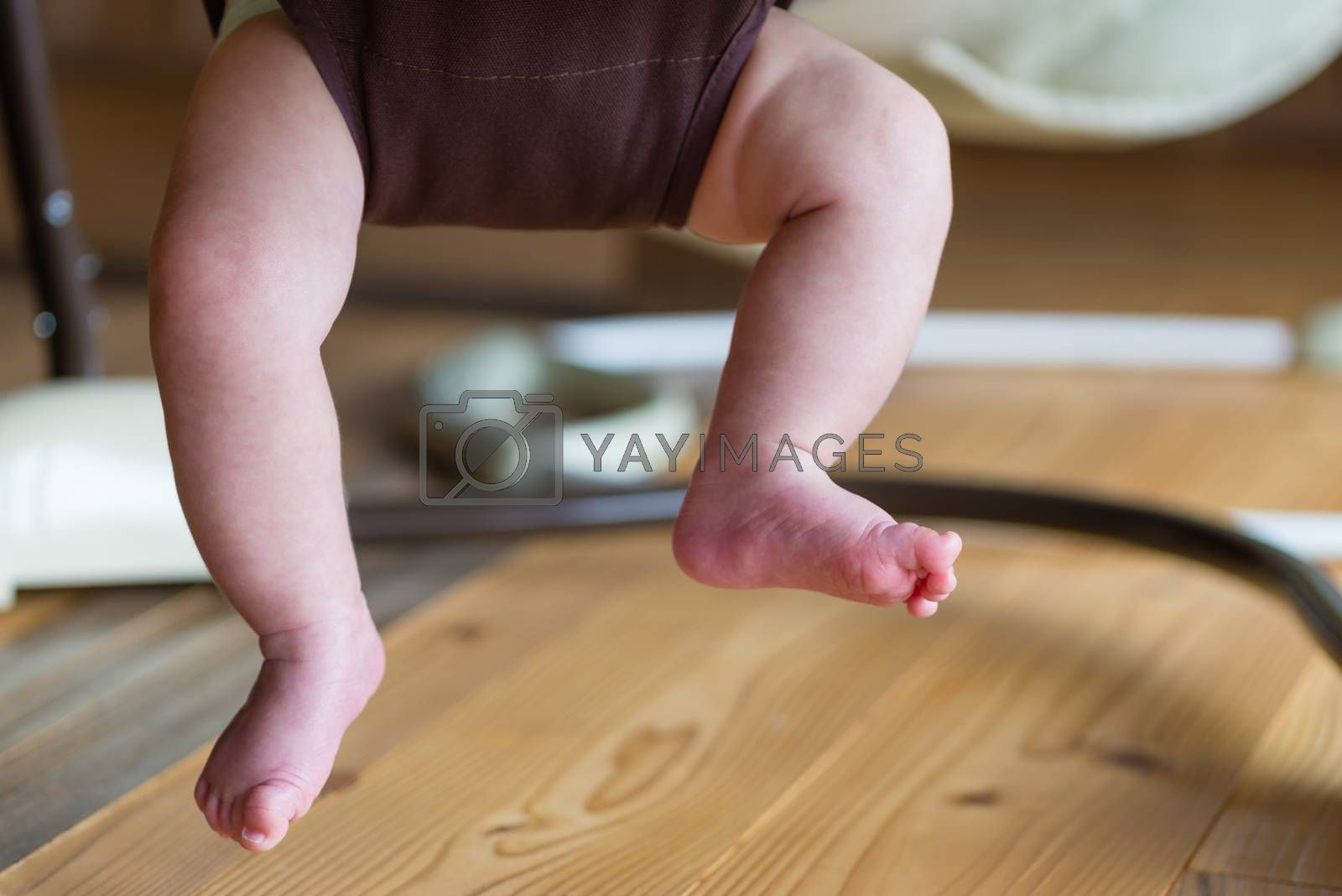 The feet and legs of a baby playing in a jumper.