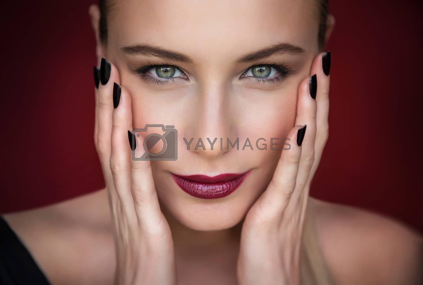 Closeup portrait of beautiful fashion model over dark red background, pretty woman with stylish makeup, beauty salon
