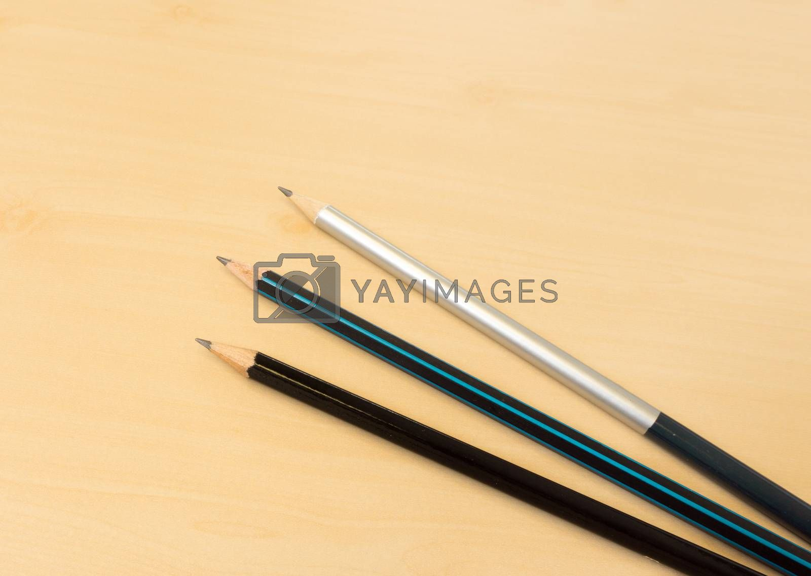 Three Color Sharp Pencils Placed on Light Brown Wooden Table Texture
