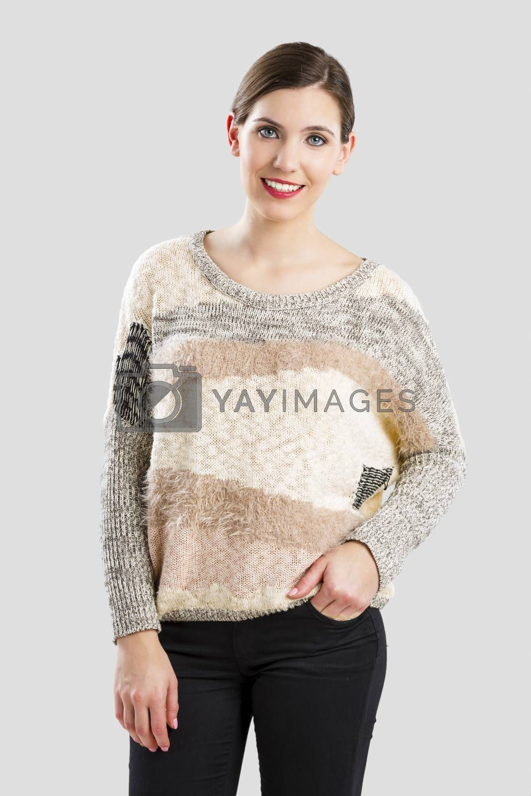 Beautiful woman smiling, isolated over a grey background