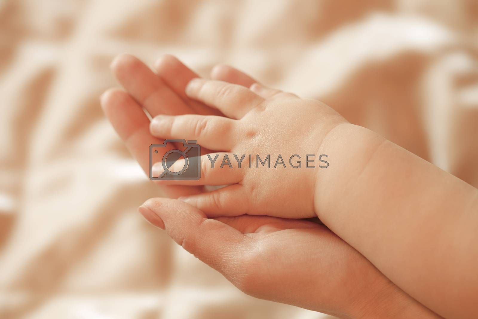 Small children's hand lies on a hand mom
